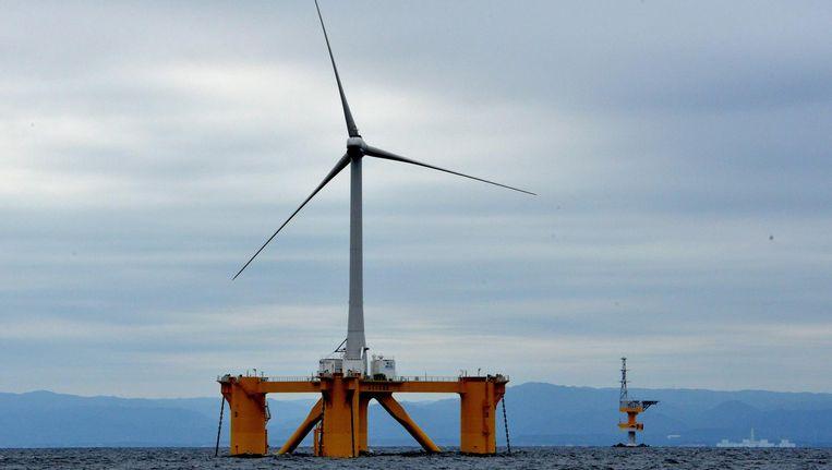 De eerste dobberende windmolen voor de kust van Fukushima, met de kerncentrale op de achtergrond. De zee is er ongeveer 150 meter diep. De turbines zijn met enorme kettingen aan de zeebodem verankerd. Beeld getty