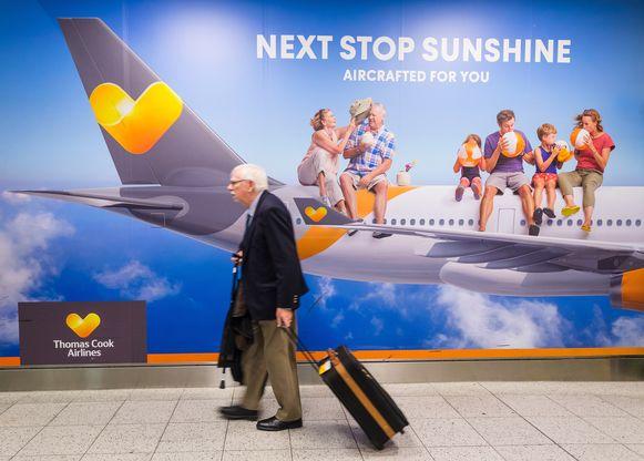 Een man loopt op een Britse luchthaven langs een billboard van Thomas Cook.