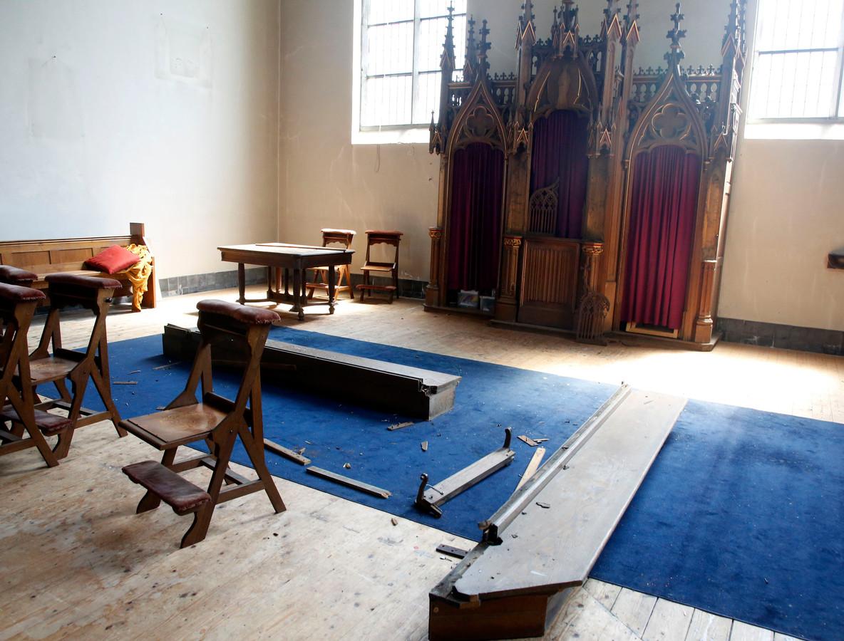 De vernielde communiebank en op de achtergrond de biechtstoel zonder de heiligenbeelden.