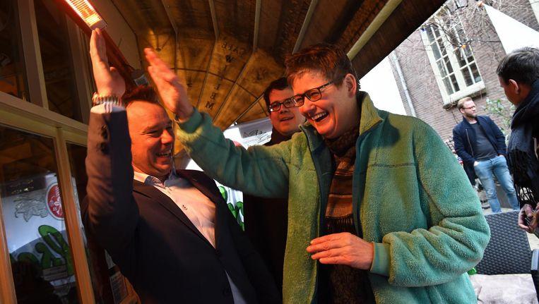 Lijsttrekkers van D66 (Klaas Verschuure, links) en GroenLinks (Heleen de Boer) in Utrecht doen een high five. Beeld Marcel van den Bergh / de Volkskrant