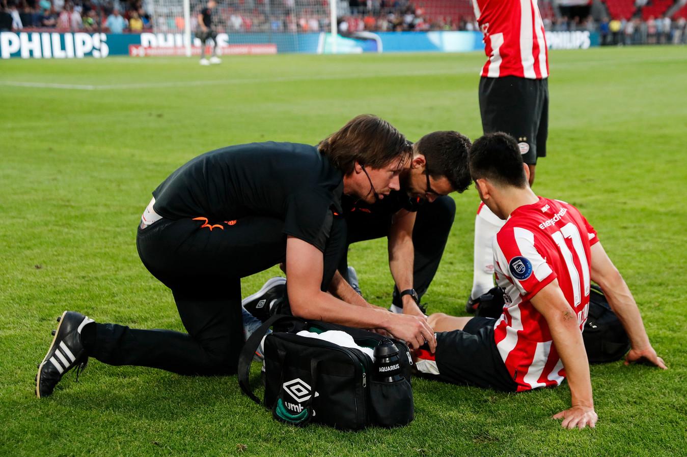 Hirving Lozano wordt in de slotfase van PSV-VfL Wolfsburg behandeld door de medische staf van PSV.