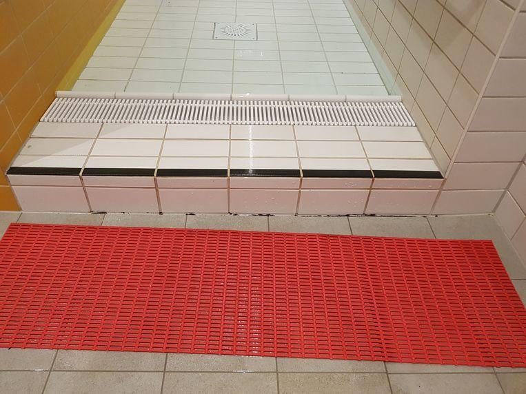 Anti-slipmatjes moeten de zwemmers helpen. Ook hier zie je de zwarte schimmel aan de tegelranden.