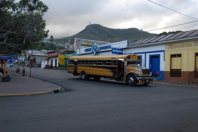 Typische Amerikaanse schoolbus, met op achtergrond de cerro Apante waarop zich een groot kruis en beeld van Virgen de Guadeloupe bevinden.