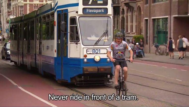 Met het filmpje wil presentator Maxim Hartman de toerist de basisprincipes van het fietsen in Amsterdam bijbrengen. Beeld Screenshot Youtube