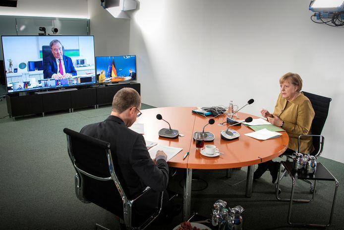 Bondskanselier Angela Merkel met Berlijns burgemeester Michael Müller (voorzitter van de deelstaatconferentie) tijdens de videoconferentie met op het scherm de minister-presidenten van de deelstaten
