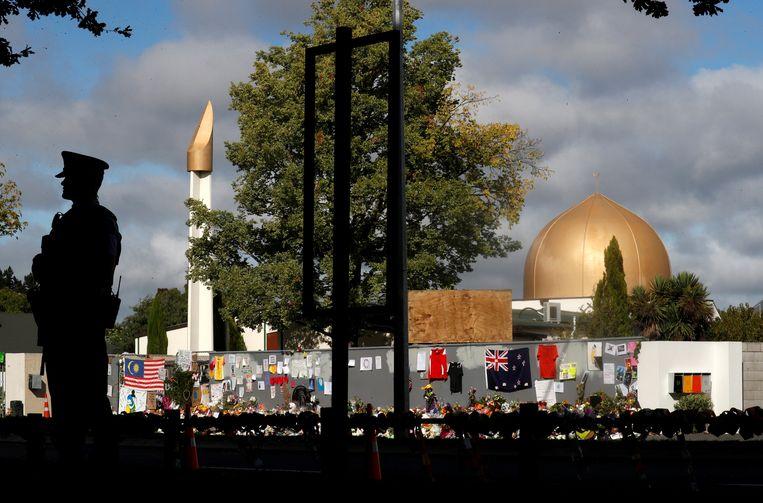 Een politieman staat buiten de Al Noor moskee in Christchurch waar Brenton Tarrant in maart het vuur opende.  Beeld REUTERS
