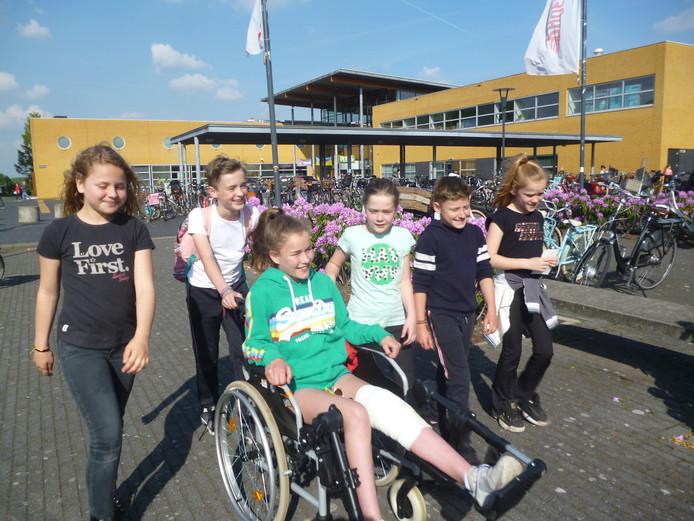 De 12-jarige Fleur, die na een knieoperatie in een rolstoel zit, wordt tijdens de Schijndelse wandelvierdaagse begeleid door (v.l.n.r.) Belle, Chris, Anouk, Jop en Loes.