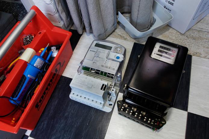 Er zijn vacatures voor mensen die slimme meters moeten monteren ter vervanging van oude elektriciteitsmeters (rechts op de foto).