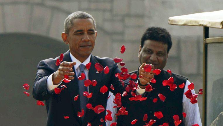 Barack Obama strooit rozenblaadjes bij het gedenkteken voor Mahatma Gandhi in New Delhi, aan het begin van zijn driedaagse bezoek aan India. Vandaag is hij eregast bij de Dag van de Republiek. Beeld EPA