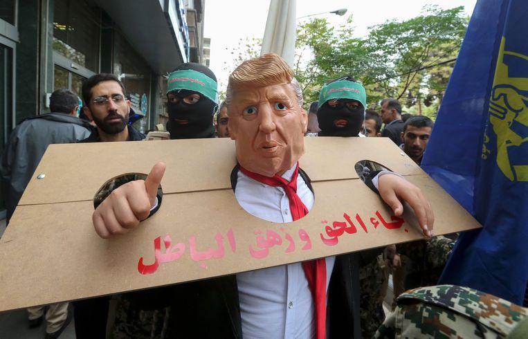 Een als president Trump vermomde betoger heeft zich in een kartonnen schandpaal gestoken.