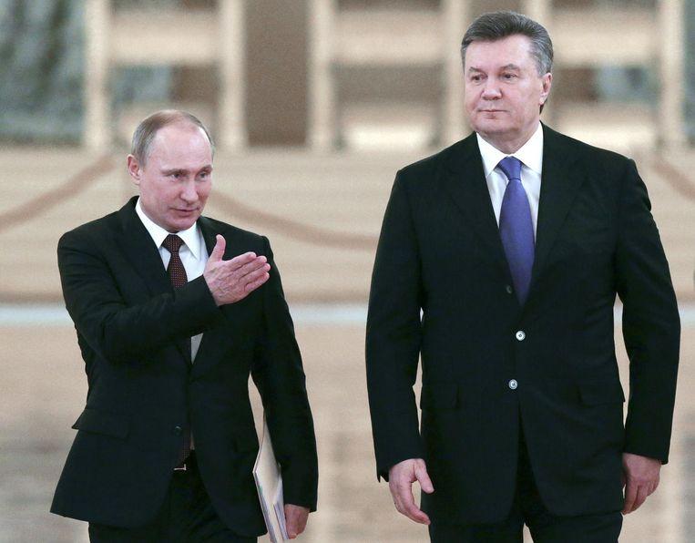 Poetin en de verdreven president Janoekovitsj. Beeld afp