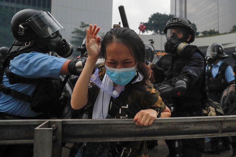 Een demonstrant wordt aangepakt door de oproerpolitie tijdens de massale demonstratie in Hongkong afgelopen woensdag.  Beeld AP