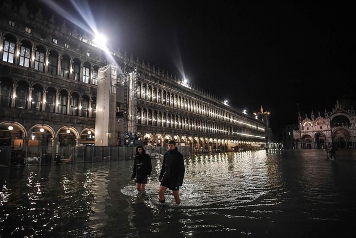Mensen lopen bijna tot aan hun knieën in het water over het San Marco-plein in Venetië.