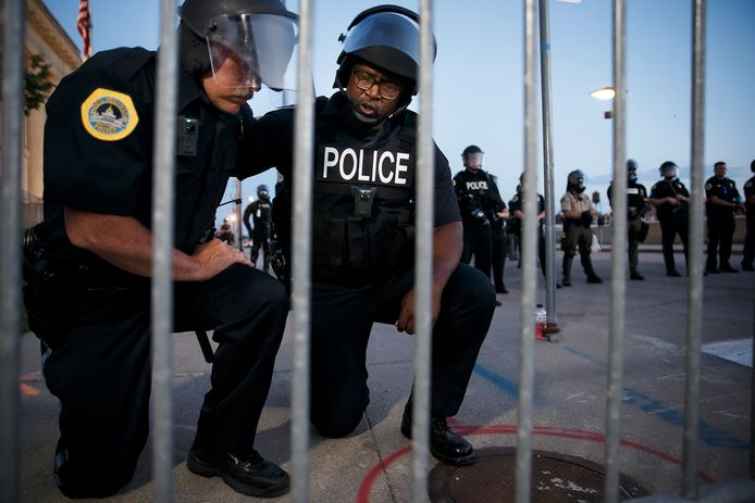 Les policiers Irvin Franklin et Jack Kamerick prient lors d'une manifestation à Des Moines.