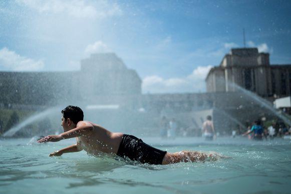 Een tiener zoekt verkoeling in de fontein van Trocadero in Parijs.