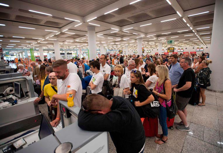 Britse vakantiegangers die bij Thomas Cook hadden geboekt, wachtten op de luchthaven van Mallorca. Beeld AFP