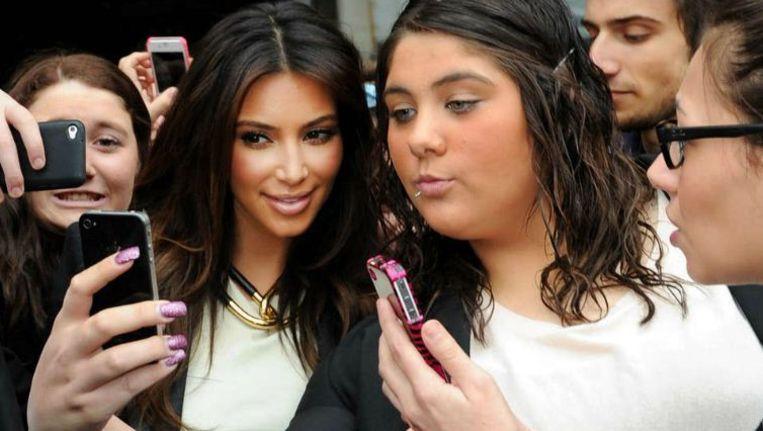 Tv-ster Kim Kardashian, omringd door fans die selfies maken. Beeld ap