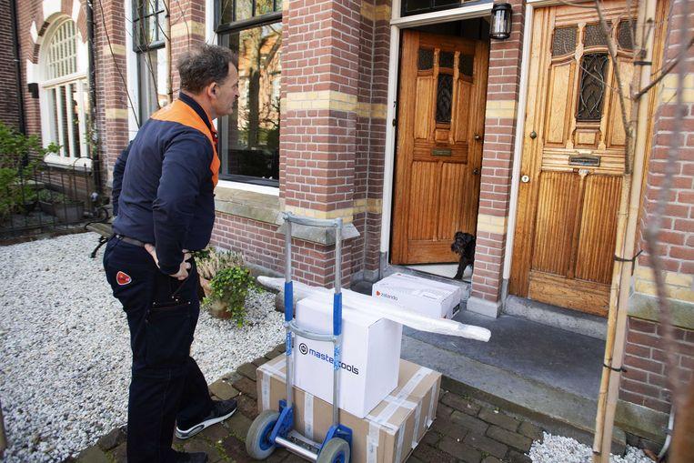 Een postbezorger doet een contactloze bezorging. Bij PostNL is het deze dagen aanzienlijk drukker dan voor de coronacrisis. Beeld ANP