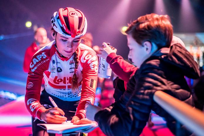 Puck Moonen is geliefd bij, vooral mannelijke, wielerliefhebbers. Bij de start van Omloop het Nieuwsblad zet ze de ene na de andere handtekening en poseert ze vaak en geduldig voor foto's.