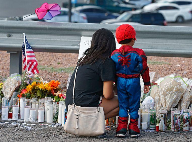 Een vrouw en een kind bij de herdenkingsplek van de aanslag in El Paso.  Beeld EPA