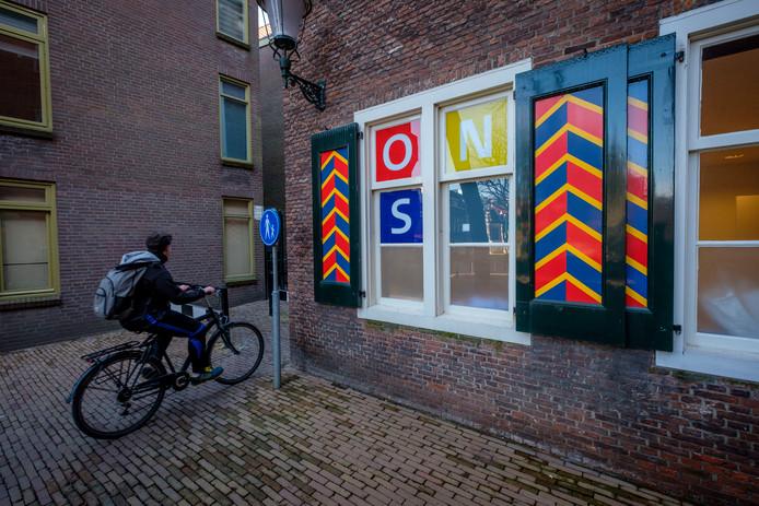 De gewraakte posters van ONS Vlaardingen achter de ramen van het gemeentehuis.