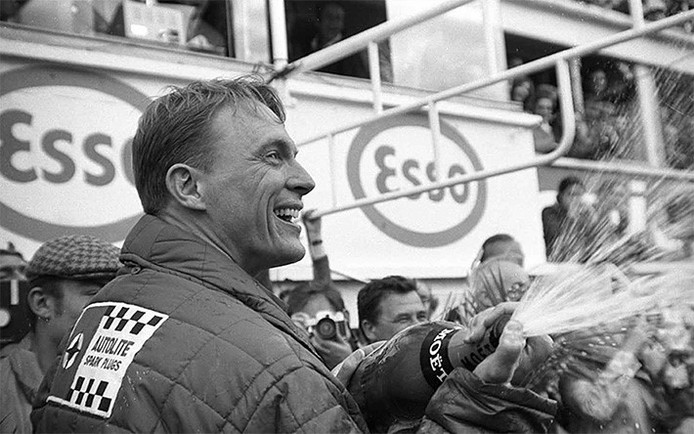 Dan Gurney begint een traditie: champagne spuiten op het podium na een gewonnen race