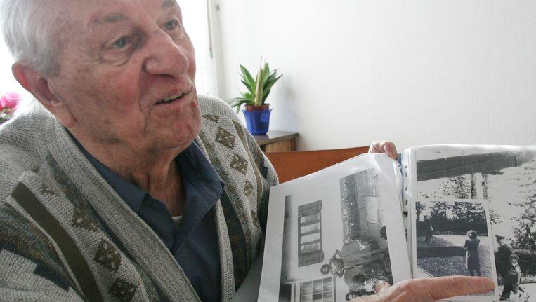 Rochus Misch laat foto's van Adolf Hitler zien. Beeld AP
