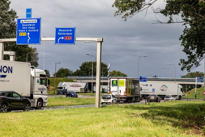 Vrachtwagens rijden af en aan op de hondenbotrotonde bij de A20 in Maasdijk.