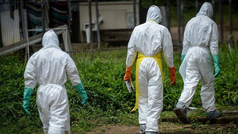Een groep vrijwilligers in draagt de lichamen van de mensen die overleden zijn aan Ebola nar een begraafplaats. Beeld getty