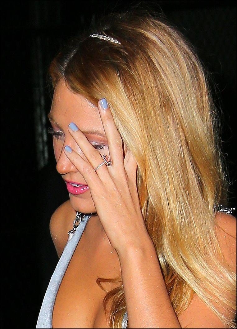 Blake Lively laat haar bijzondere verlovingsring (een beetje) zien. Het is een ovalen, lichtroze diamant gedragen door een ring van kleinere diamanten.