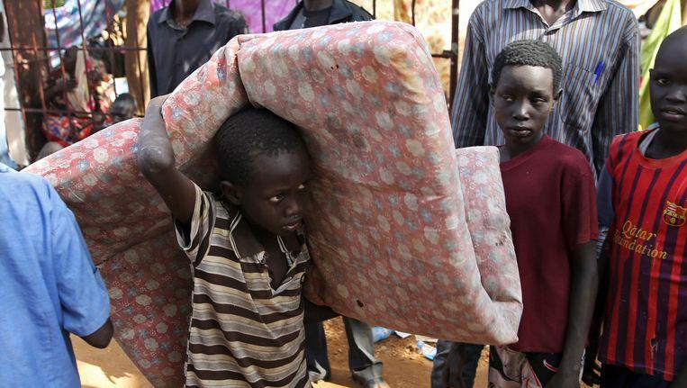 Een jonge vluchteling tilt een matras. Beeld REUTERS
