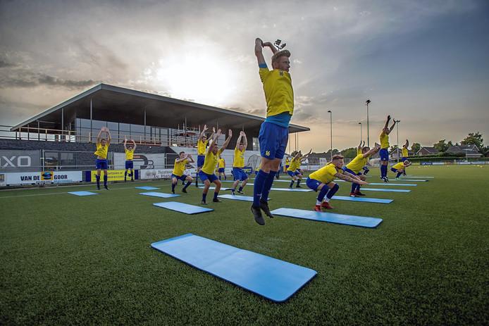 Het eerste van Berghem Sport in training, met op de achtergrond het clubgebouw in aanbouw.