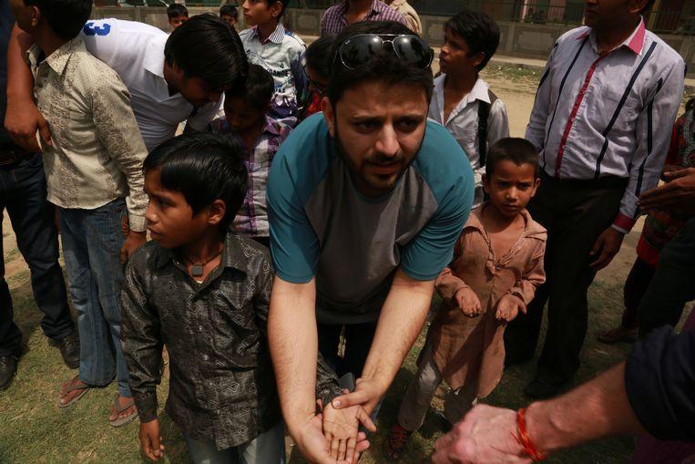 Tijdens een reddingsactie van Indiase kinderen die gedwongen werk verrichten laat een man zien dat het jongetje lijm op zijn hand heeft. Vormen van slavernij komen vooral voor in arbeidsintensieve sectoren zoals de landbouw, de bouw, de detailhandel, de textielindustrie en de mijnbouw. Beeld Basit Jamal