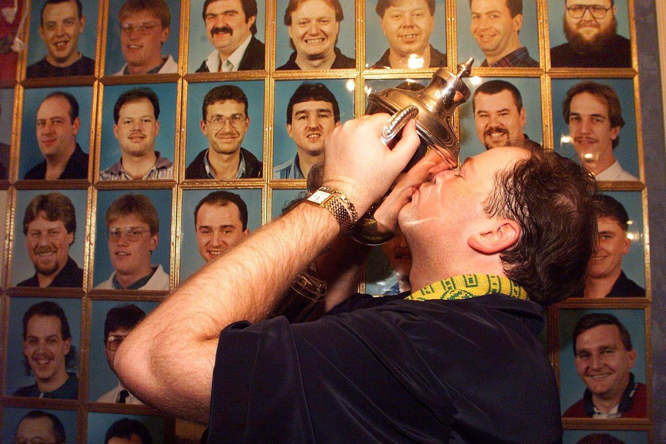 1999: Raymond van Barneveld wint het WK in Frimley Green en kust de trofee. Op de achtergrond de Hall of Fame, met de portretten van de winnaars van het Embassy World Darts door de jaren heen.