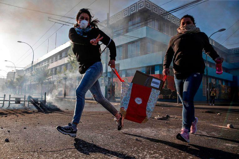 Plunderaars met hun buit in Valparaíso. Beeld AFP