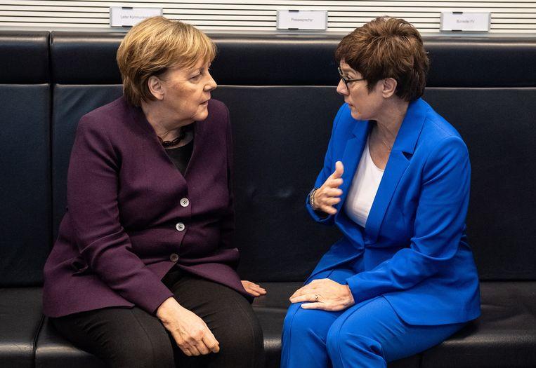 Angela Merkel in gesprek Annegret Kramp-Karrenbauer tijdens een partijmeeting in januari. Nu heeft Kramp-Karrenbauer plots aangekondigd geen kandidaat-bondskanselier meer te zijn.