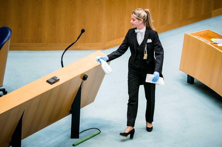 Een kamerbode maakt de interruptiemicrofoon schoon tijdens een debat over de ontwikkelingen rondom het coronavirus.  Beeld null