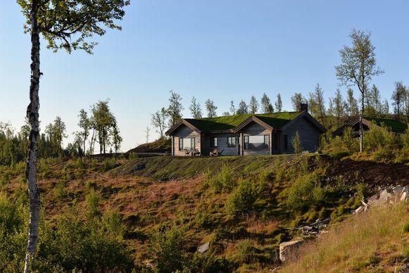 Het gezin liet vlak bij een berg en dicht bij een meer een hut bouwen die door het groene dak en de verweerde houten gevel opgaat in de omgeving.