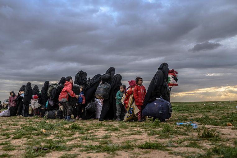 Vrouwen en kinderen die zojuist Baghouz hebben verlaten, wachten om te worden gecontroleerd door de SDF.  Beeld AFP