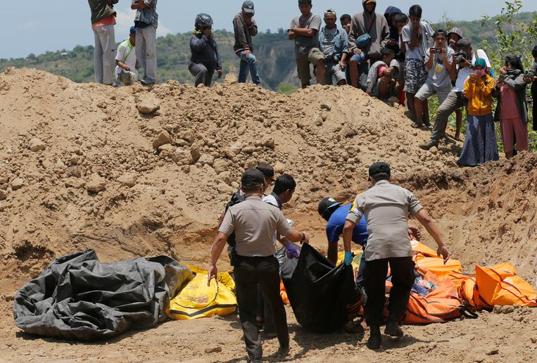 In Palu worden de gevonden lichamen naar een massagraf gebracht.