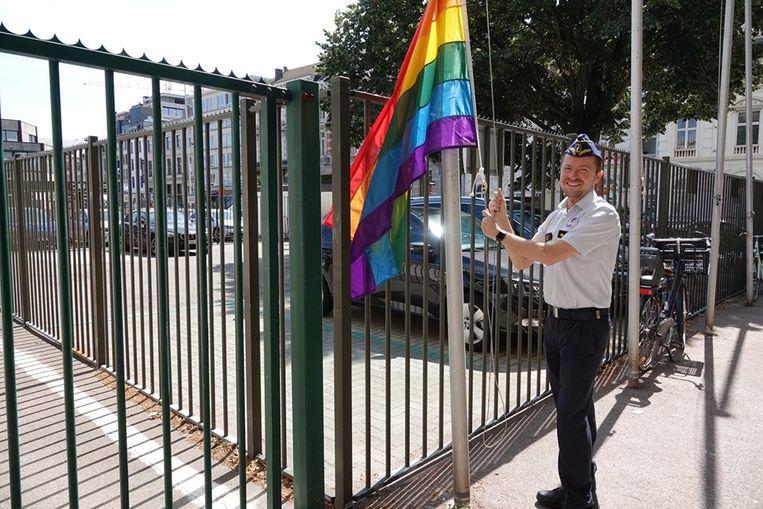 De korpschef heist de regenboogvlag in de Oudaan.