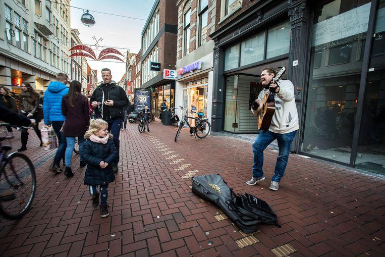 Een straatmuzikant treedt op voor een leegstaand winkelpand in een winkelstraat in Leiden. Beeld ANP, Alexander Schippers