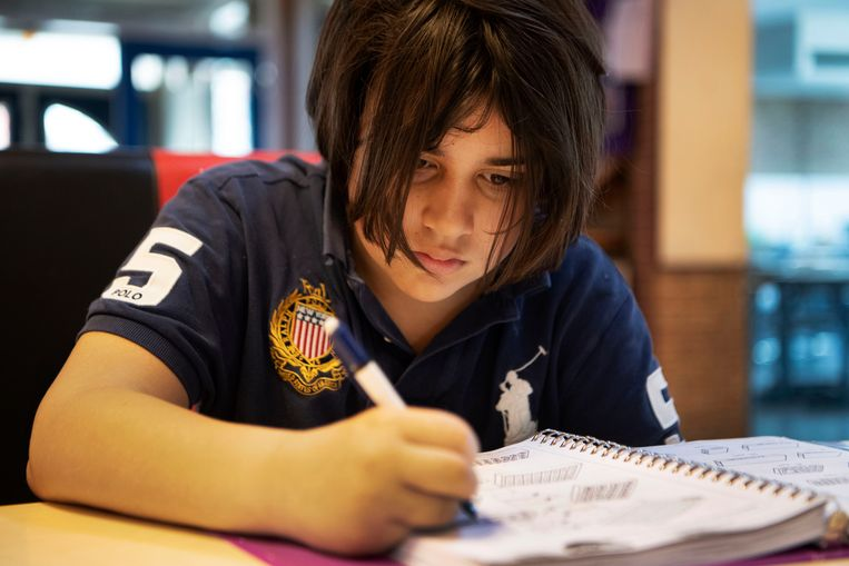 Angelo (12) maakt huiswerk bij basisschool Wereldwijs in Zuid-Oost. Beeld Olaf Kraak