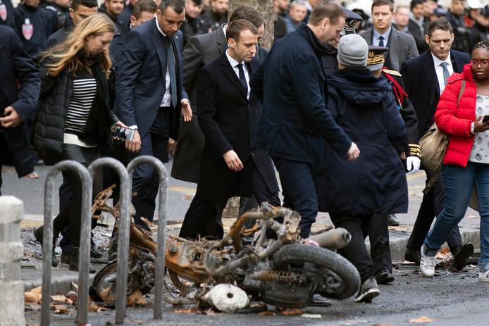 President Emmanuel Macron (m) bekijkt met eigen ogen de schade die de 'gele hesjes' gisteren aanrichtten.