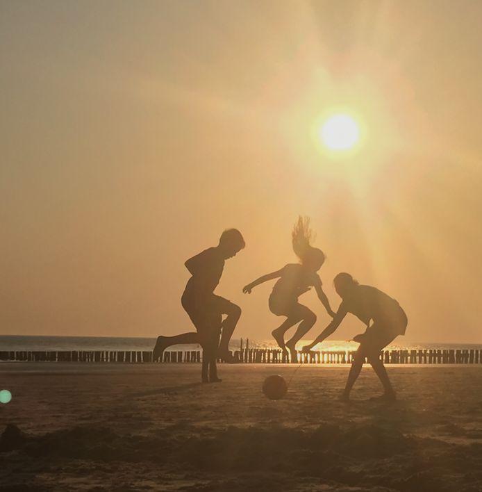 GELUKSGEVOEL Heerlijk spelen met de bal op het strand in de late avondzon. Volop plezier maken op het strand van Zoutelande.