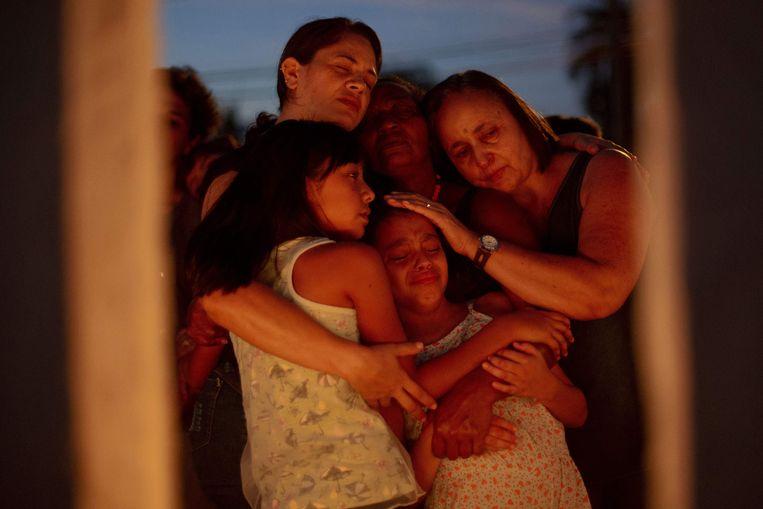 Mensen troosten elkaar tijdens de wake in Brumadinho.