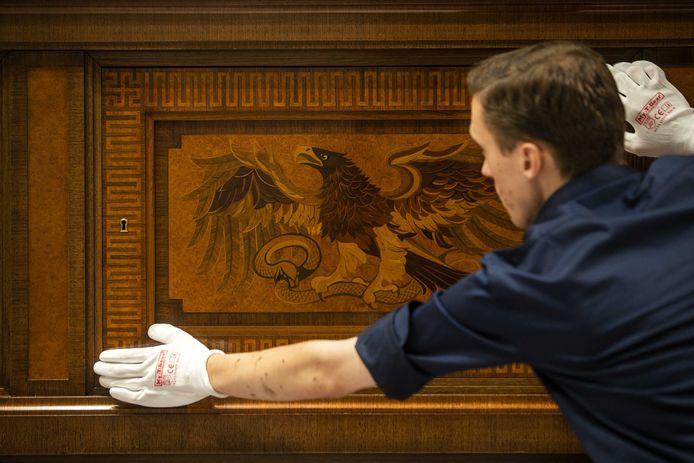 Een dressoir van Hitler, met adelaar en hakenkruisen (in de hoek) wordt uitgepakt tijdens de opbouw.
