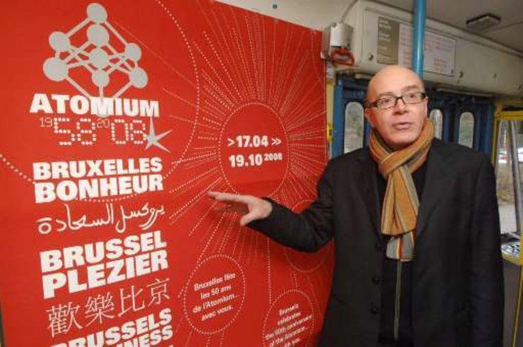 Henry Simons, de directeur van de vzw Atomium, naast een van zijn affiches.