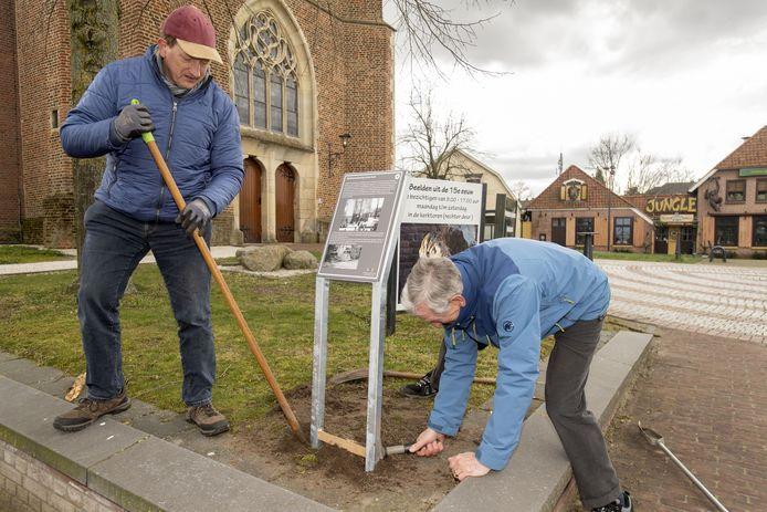 Dinant Rohaan (links) en Niels Sies van het 4 en 5 mei comité Neede plaatsen op het Kerkplein het informatiebord over de klokkenroof in Neede. @ Frans Nikkels