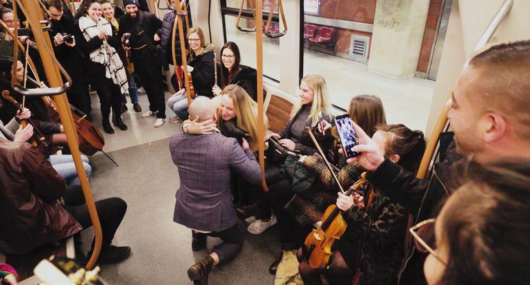 Jérémy gaat op één knie op de metro, onder begeleiding van het orkest.